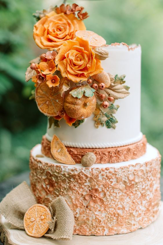 a sophisticated fall wedding cake with rust floral patterns, fresh orange blooms, faux citrus slices and pumpkins