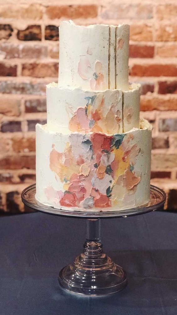 a wedding cake with colorful brushstrokes and a gold edge plus a rough edge for a catchy look
