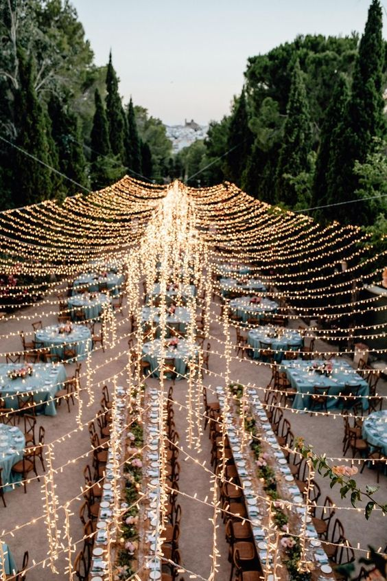 an oversized light canopy over the lovely and pretty rustic wedding reception outdoors creates a festive mood at once