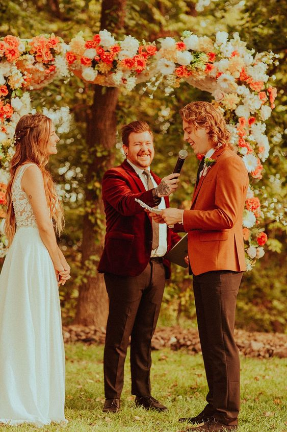black pants, black shoes, a white shirt, a black tie and an orange blazer for a bold summer boho wedding