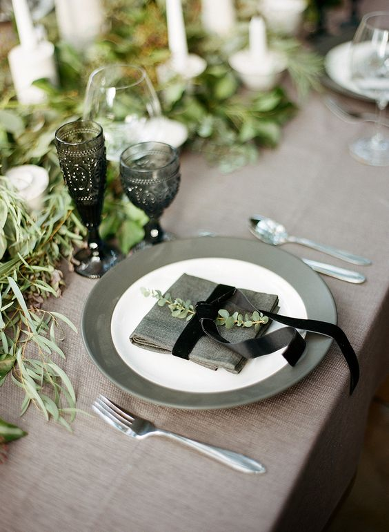 a Scandinavian wedding tablecape with a greenery runner, candles, smoked glasses, grey plates and neutral linens