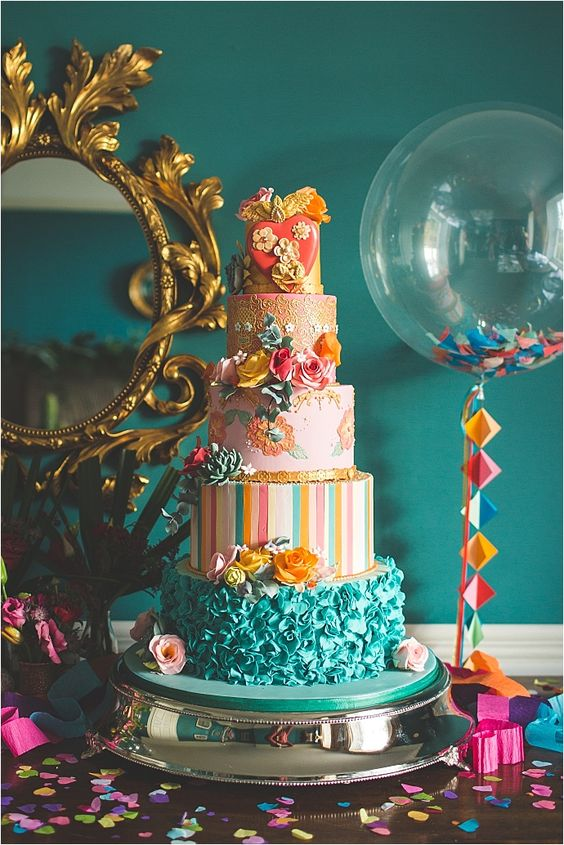 a bright wedding cake with a yellow, lace, floral, striped and ruffle tier, sugar blooms and succulents is a very whimsical idea