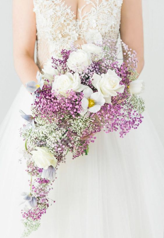 a cascading wedding bouquet with white roses, pink, purple and white baby's breath is a very beautiful idea