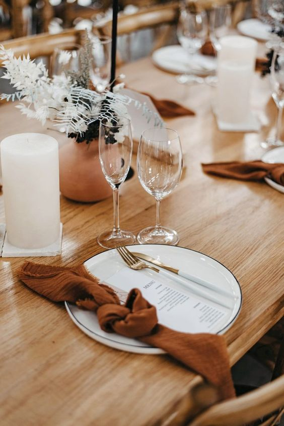 a minimalist wedding tablescape with terracotta vases and dried blooms, white candles, menues and rust napkins
