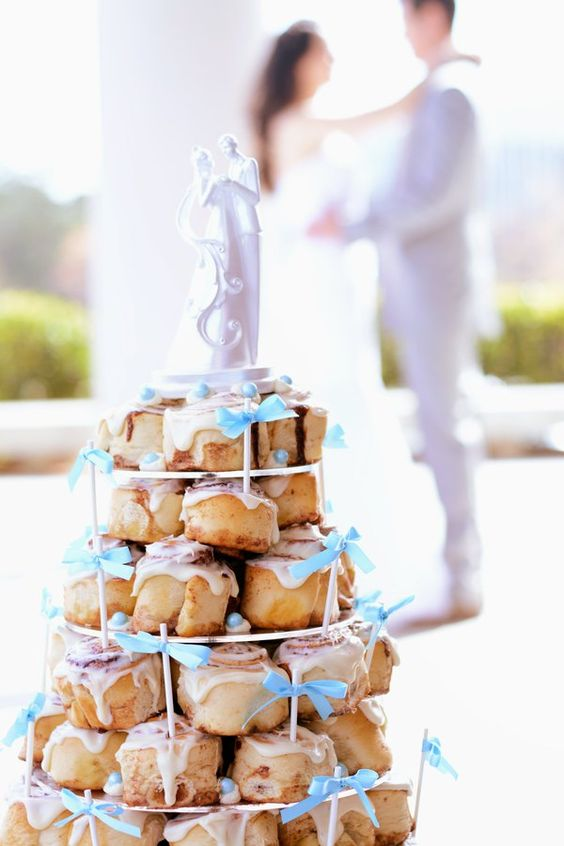 a stand with cinnamon buns on skewers with bows is a pretty and cute dessert idea for any wedding