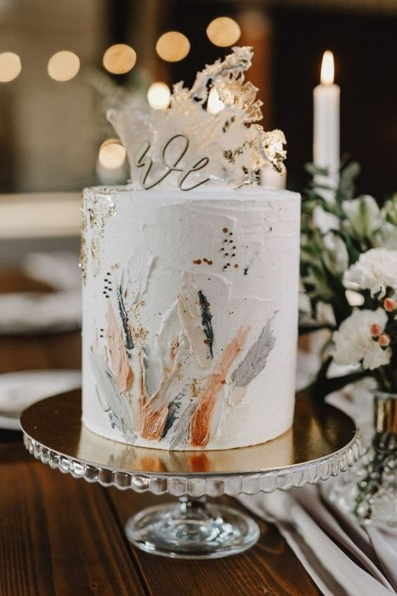 a white textural wedding cake with colorful brushstrokes, some sugar waves and a calligraphy topper