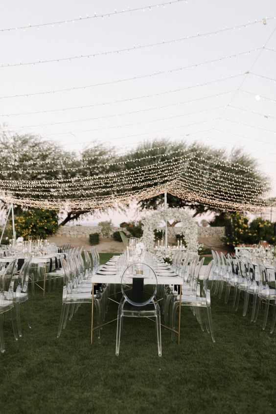 an ultra-modern white wedding reception with ghost chairs and a delicate light canopy is very chic and cool