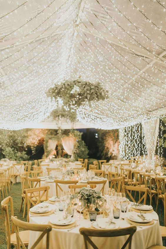 a chic and refined neutral wedding reception with a light canopy and eucalyptus chandeliers, with greenery centerpieces and neutral linens