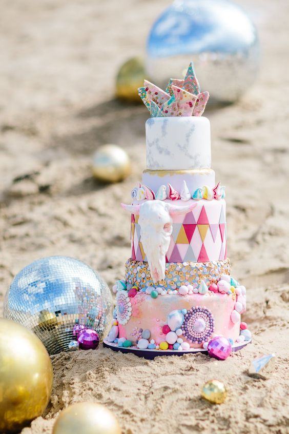 a colorful and crazy wedding cake with mismatching and bright detailed tiers, with colorful shards and a faux skull for a Burning Man wedding