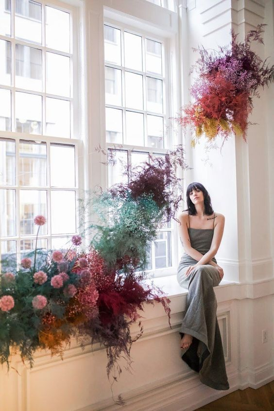 a colorful floral installation of bright baby's breath and smoke bush is a gorgeous decor idea for any space
