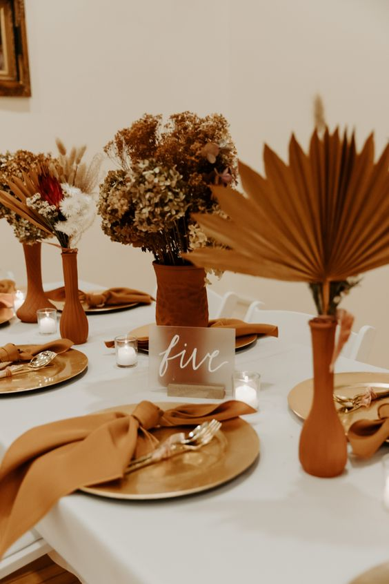 a modern boho wedding tablescape with terracotta vases with dried blooms and fronds, rust napkins and metallic plates
