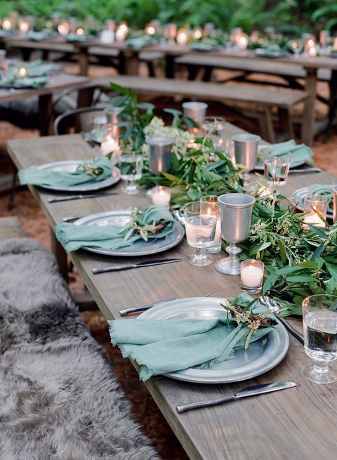 a simple and rustic Scandinavian tablescape with green linens, a greenery runner, candles and goblets is chic