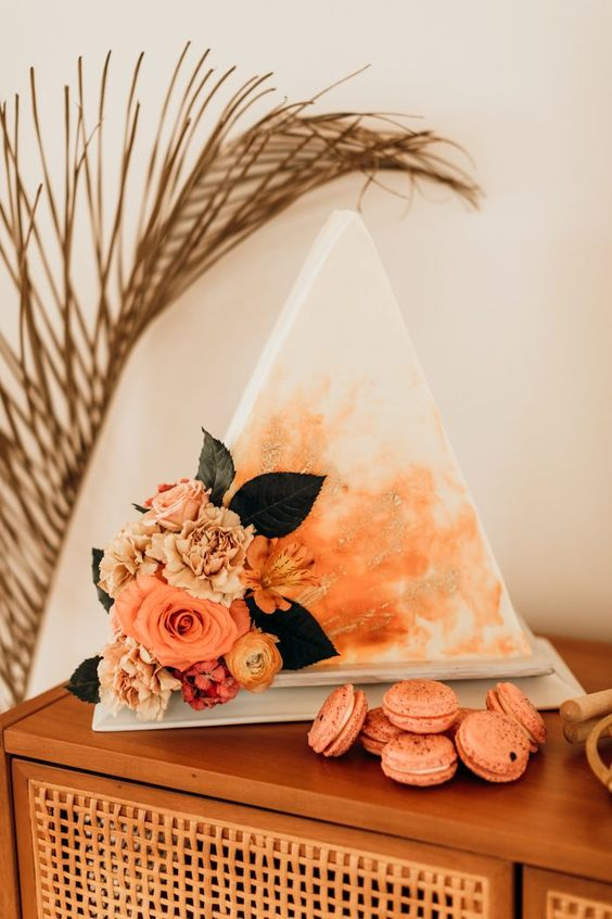 a unique triangle wedding cake with rust watercolors and gold leaf plus fresh bright blooms and leaves on one corner
