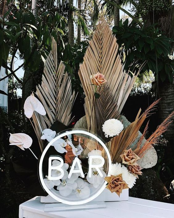 a bar floral arrangement - white and rust blooms, dried fronds and some grass plus a neon sign for a chic look