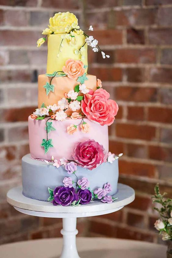 a colorful wedding cake with each tier in a different pastel shade plus matching sugar blooms and blooming branches wows