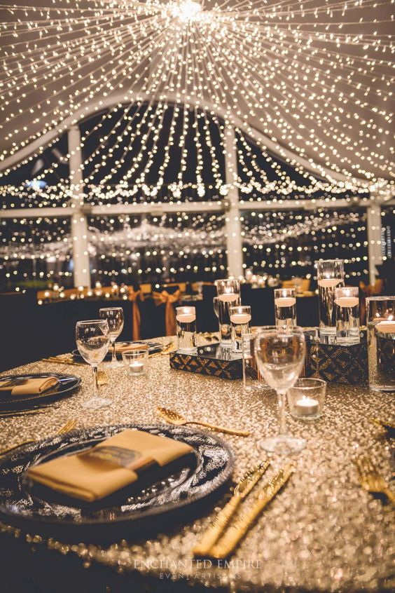 a glam Great Gatsby wedding reception with a large light canopy over the space is all sparkling and fun