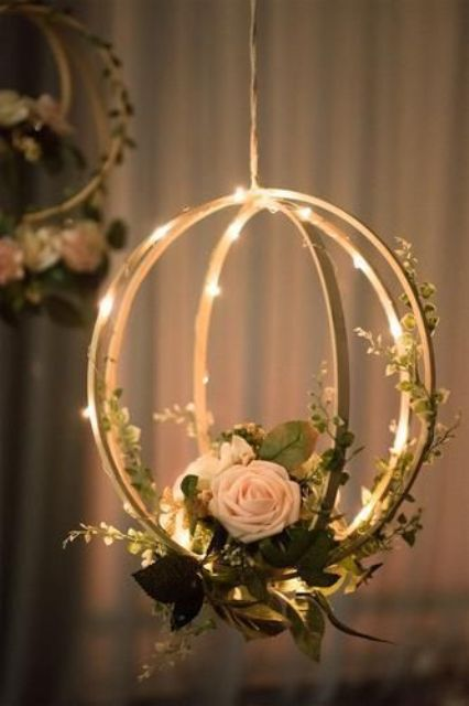 a hanging sphere with a floral arrangement and lights is a very creative alternative to a usual centerpiece