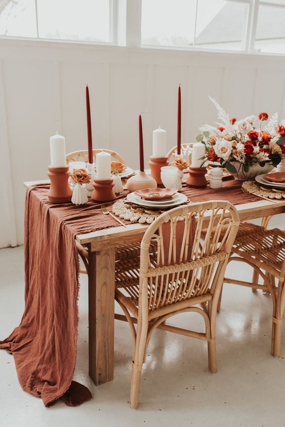 a pretty boho wedding tablescape with a rust fabric table runner, rust candles, terracotta candleholders and bright blooms