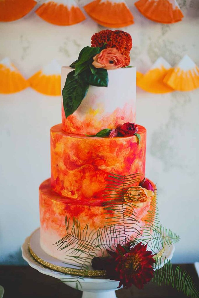 a white wedding cake with bright red and orange watercolors, fresh blooms and leaves will be a gorgeous idea for a colorful wedding