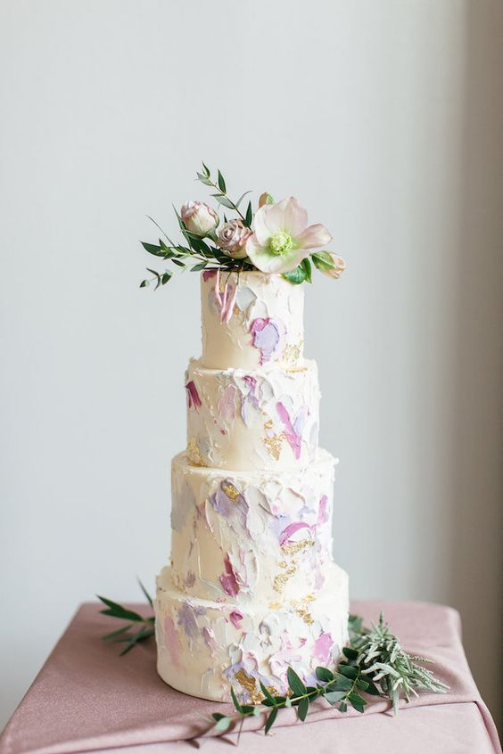 a white wedding cake with white, lilac and purple brushstrokes, gold leaf and pastel blooms on top