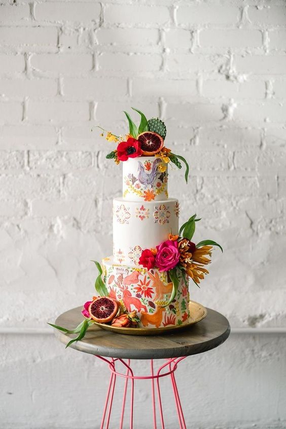 a colorful wedding cake with handpainted animals and birds, painted and fresh bold blooms, a cactus and some citrus