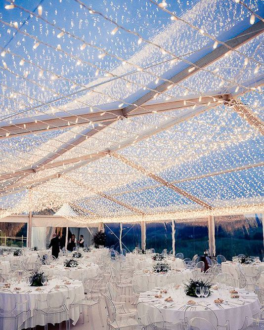 a jaw-dropping white tent wedding reception with all white linens, greenery centerpieces and a large white light canopy over the space