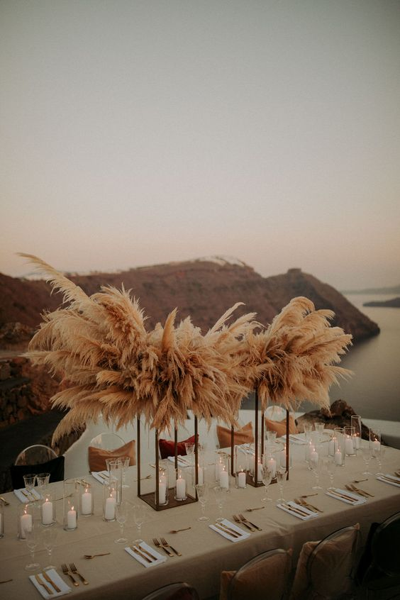38 a lush wedding centerpiece of lots of pampas grass on tall stands and candles lining up the table for a boho wedding
