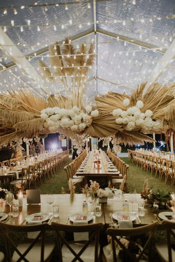 a luxurious wedding reception in a tent, with lights, pampas grass, dried fronds and white blooms plus candles on the tables