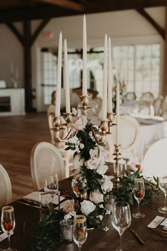 a refined candelabra interwoven with white roses and greenery and with tall candles