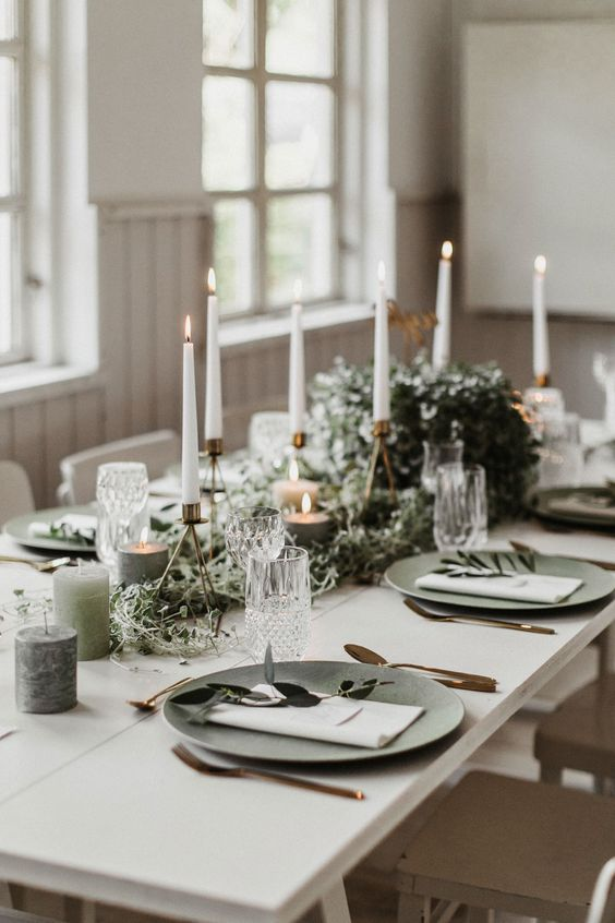a stylish and fresh Nordic wedding tablescape with green plates, candles, greenery decor and copper cutlery