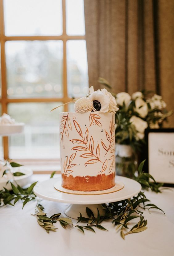 a white wedding cake with painted rust leaves and white fresh blooms on top is a beautiful idea for a modern wedding