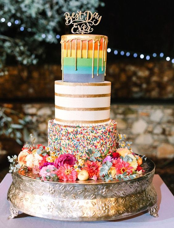 a fun and colorful wedding cake with a rainbow, striped and sprinkle tier, with gold drip, bold blooms and greenery and gold calligraphy