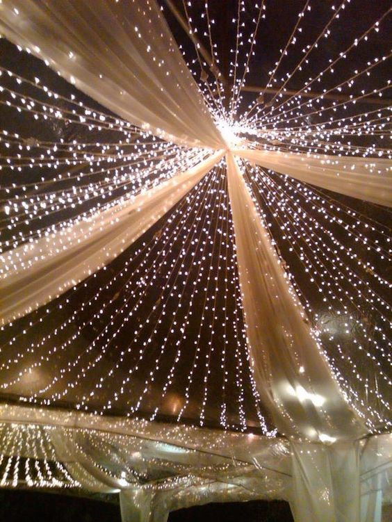 a large light canopy with white fabric is a stylish idea for many indoor weddings, it's timeless