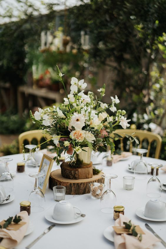 a lush neutral floral arrangement with greenery in a bucket on wood slices is a lovely idea for a rustic wedding