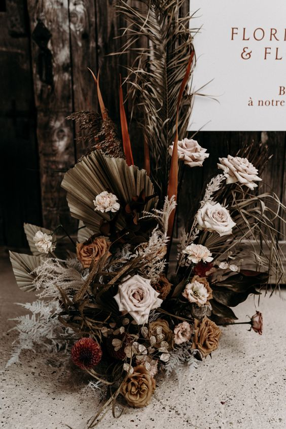 a moody floral wedding decoration of green dried palm leaves, pale pink, burgundy and rust blooms, dried foliage for a boho wedding