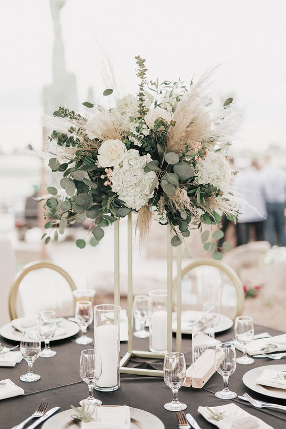 a pretty tall wedding centerpiece of eucalyptus, white blooms and pampas grass for a modern wedding with a boho touch