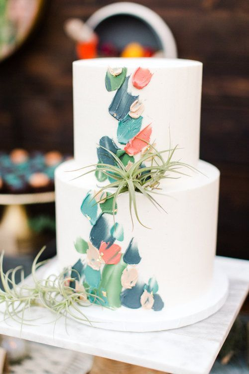 a simple mid-century wedding cake with colorful brushstrokes and air plants is a cool and very cheerful idea
