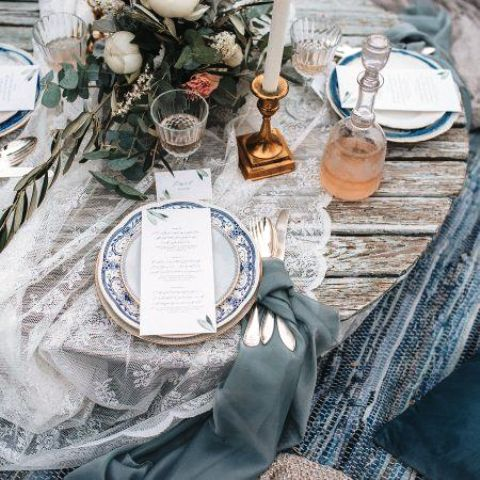 a winter Scandinavian wedding tablescape with a lace runner, grey napkins, printed plates, a white floral centerpiece and candles