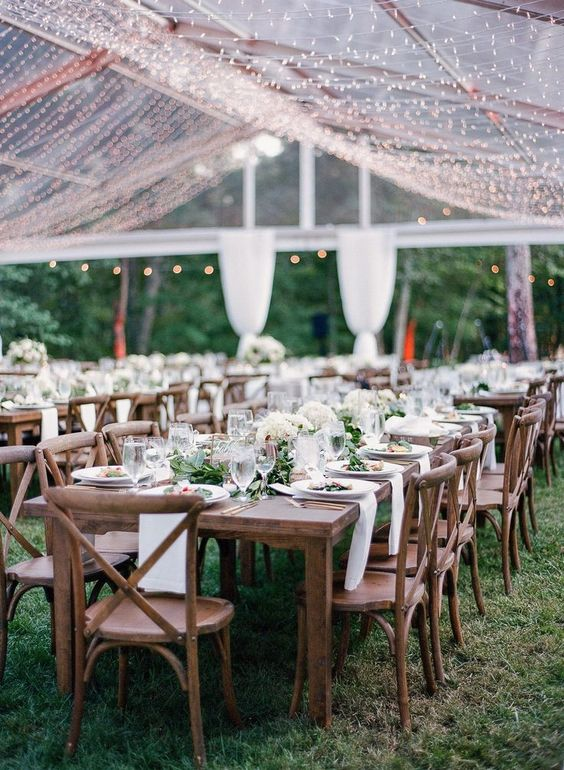 a lovely and chic tent wedding reception with wooden tables and chairs, white linens and a warm white light canopy