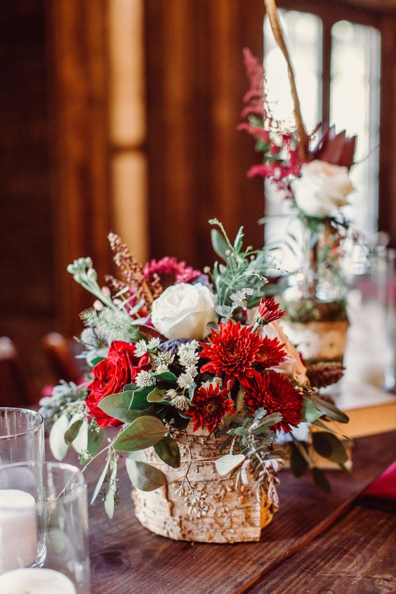 a lovely bold wedding centerpiece of various blooms and greenery wrapped in bark is a chic idea