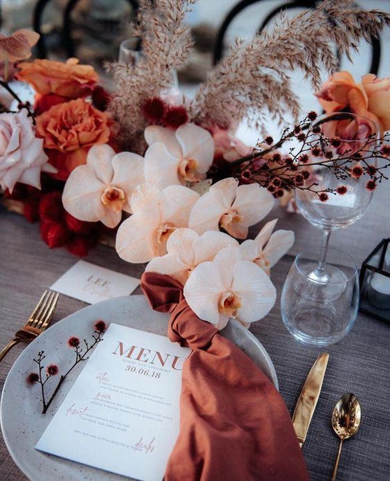 a pretty modern wedding tablescape with rust napkins, rust and blush florals and grasses and gold cutlery
