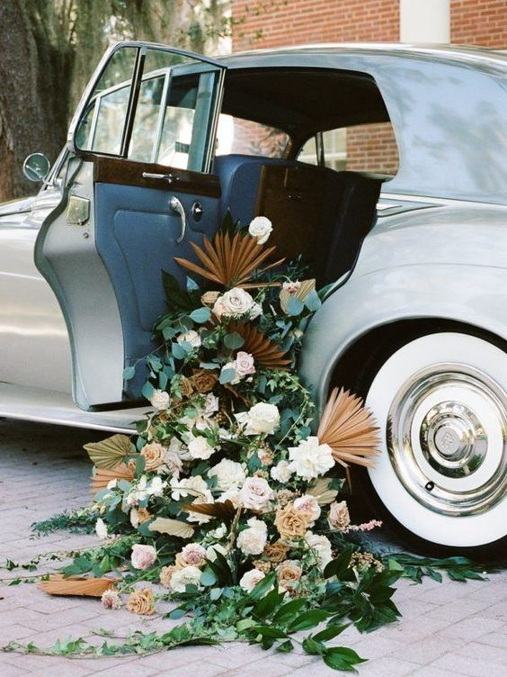a vintage car filled with greenery, blush and white blooms, dried fronds is a refined and chic decoration for a wedding