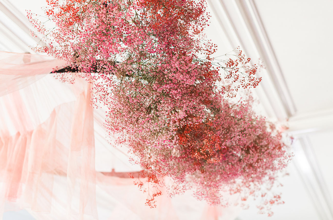 a wedding chandelier with pink tulle and pink and red baby's breath is a very bold and cool idea to rock