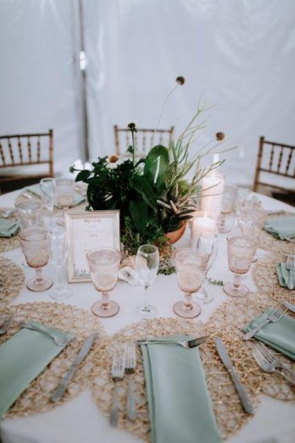 a beautiful boho greenery and cacti wedding centerpiece with some cascading greenery and a framed table name