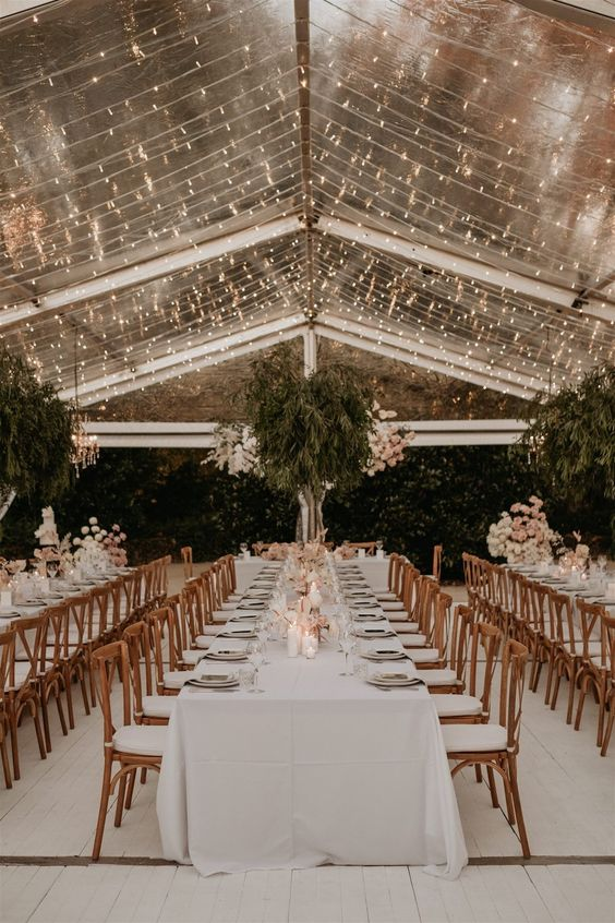 a luxurious clear tent with a light canopy under the roof, with oversized greenery and bloom installations