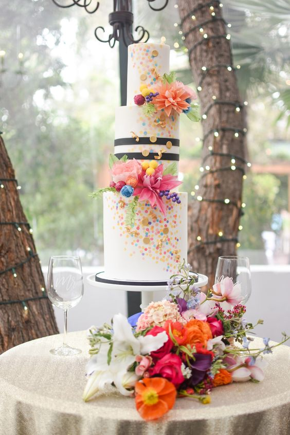 a playful wedding cake with colorful sprinkle and a striped tier, bold sugar blooms and berries all over the cake