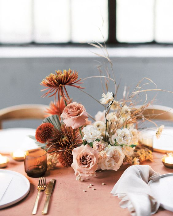 a refined wedding table setting with a terracotta tablecloth, rust, blush and white blooms and grasses and amber glasses