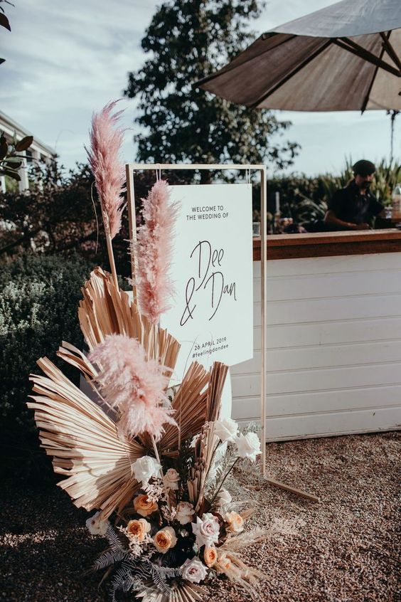 a wedding decoration - a sign hanging on a frame pink pampas grass, dried fronds and white and peachy blooms is cool
