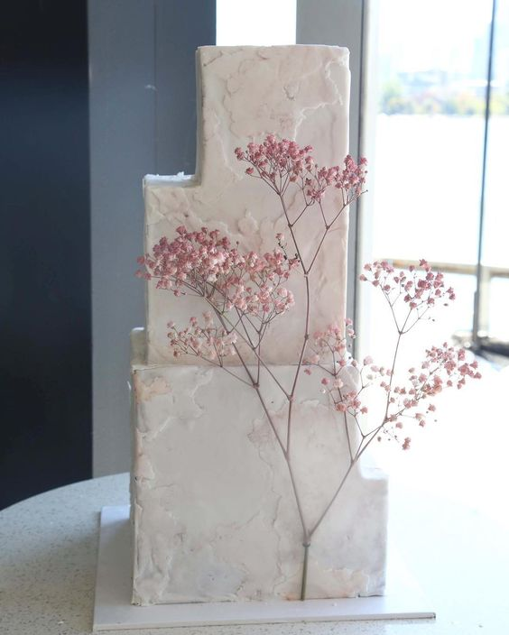 a white textural buttercream wedding cake decorated with pink baby's breath is a very refined and elegant idea