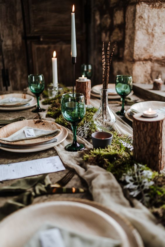 a woodland Nordic table setting with a fabric and moss runner, tree stumps, candles, feathers and wooden plates